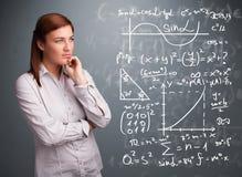 Belle fille d'école pensant aux signes mathématiques complexes Photo stock