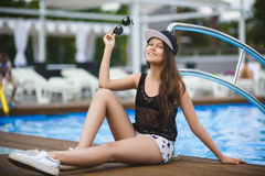 Belle fille d'adolescent s'asseyant près de la piscine extérieure Photographie stock libre de droits