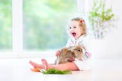 Belle fille d'enfant en bas âge avec les cheveux bouclés avec le vrai lapin Photo stock