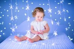 Belle fille d'enfant en bas âge jouant avec son ours de jouet entre les lumières molles dans la forme d'étoile Image libre de droits