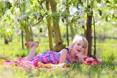 Belle fille d'enfant en bas âge jouant dans l'orhcard de floraison de fruit Photographie stock libre de droits