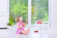 Belle fille d'enfant en bas âge jouant des maracas dans la chambre blanche Image libre de droits