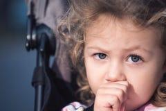 Belle fille d'enfant en bas âge suçant son pouce dans une poussette photographie stock libre de droits