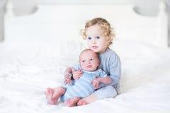 Belle fille d'enfant en bas âge tenant son frère nouveau-né de bébé sur un whi Photographie stock