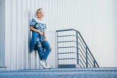 Belle fille d'image avec les cheveux blancs courts Habillé dans des jeans dans le style urbain Place pour le texte image stock
