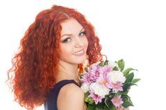 Belle fille d'une chevelure rouge avec fleurs Images stock