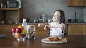 Belle fille dans des écouteurs dansant dans la cuisine banque de vidéos