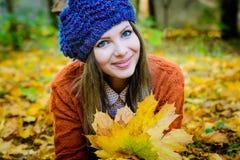 belle fille dans des feuilles d'automne Image stock