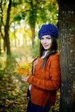 belle fille dans des feuilles d'automne Photos stock