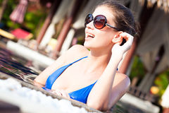 Belle fille dans des lunettes de soleil dans la piscine de luxe Photos stock