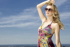 Belle fille dans des lunettes de soleil sur le ciel bleu Image stock