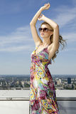 Belle fille dans des lunettes de soleil sur le ciel bleu Image libre de droits