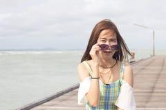 Belle fille dans des lunettes de soleil sur le pont et la mer en bois Photographie stock libre de droits