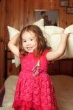 Belle fille dans des oreillers de jets d'une robe image libre de droits