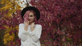 Belle fille dans des poses de chapeau à l'arbre de rose d'automne avec le sourire sur le visage clips vidéos