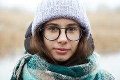 Belle fille dans des verres ronds et un chapeau tricoté Photo libre de droits