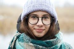 Belle fille dans des verres ronds et un chapeau tricoté Images stock