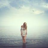 Belle fille dans l'eau Plage, lever de soleil, froid Images stock