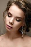 Belle fille dans l'image d'une jeune mariée avec les boucles d'oreille lumineuses Modelez avec un maquillage doux dans des tons b Photos libres de droits