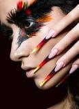 Belle fille dans l'image de l'oiseau de Phoenix avec le maquillage créatif et les longs clous Conception de manucure Visage de be Photo stock
