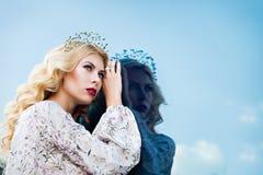 Belle fille dans l'image de la reine de neige Peau claire, cheveux blancs, une couronne sur sa tête Photographié sur la rue Photos stock