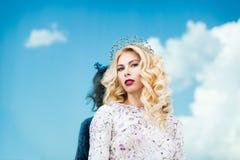 Belle fille dans l'image de la reine de neige Peau claire, cheveux blancs, une couronne sur sa tête Photographié sur la rue Photographie stock libre de droits