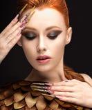 Belle fille dans l'image de Phoenix avec le maquillage lumineux, les longs ongles et les cheveux rouges Visage de beauté Images stock