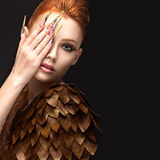 Belle fille dans l'image de Phoenix avec le maquillage lumineux, les longs ongles et les cheveux rouges Visage de beauté Images libres de droits