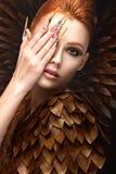 Belle fille dans l'image de Phoenix avec le maquillage lumineux, les longs ongles et les cheveux rouges Visage de beauté Photo libre de droits