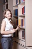 Belle fille dans la bibliothèque Photo stock