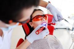 Belle fille dans la chaise du ` s de dentiste Image stock