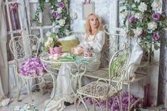 Belle fille dans la chambre avec des fleurs Photo stock
