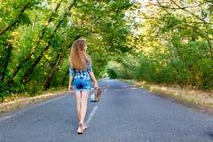 Belle fille dans la chemise de plaid bleue marchant sur un betw vide de route photos stock