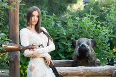 Belle fille dans la robe blanche posant avec un fusil de chasse photo stock