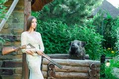 Belle fille dans la robe blanche posant avec un fusil de chasse et un verrat bourré sur le fond image stock