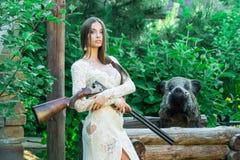 Belle fille dans la robe blanche posant avec un fusil de chasse et un verrat bourré sur le fond images stock