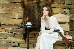 Belle fille dans la robe blanche posant avec un fusil de chasse sur le fond d'une peau d'ours images libres de droits