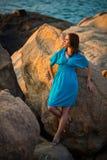 Belle fille dans la robe bleue au milieu de grands rochers sur le fond de mer photos stock
