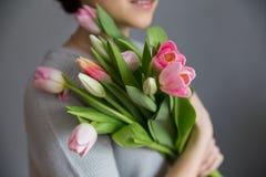 Belle fille dans la robe bleue avec des tulipes de fleurs dans des mains sur un fond clair Images libres de droits