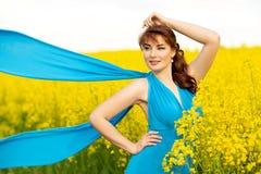 Belle fille dans la robe bleue avec les fleurs jaunes photographie stock