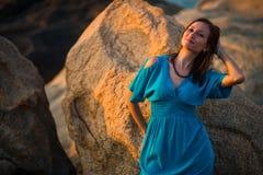 Belle fille dans la robe bleue posant contre de grandes pierres au coucher du soleil image stock