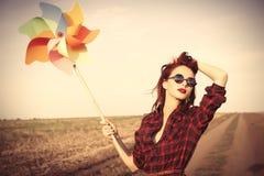 Belle fille dans la robe de plaid avec le jouet de vent Image stock