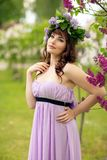 Belle fille dans la robe pourpre avec les fleurs lilas images stock