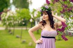 Belle fille dans la robe pourpre avec les fleurs lilas images libres de droits