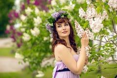 Belle fille dans la robe pourpre avec les fleurs lilas photos libres de droits