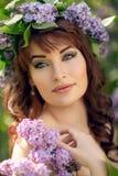 Belle fille dans la robe pourpre avec les fleurs lilas photos stock
