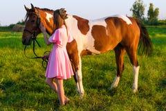 Belle fille dans la robe rose avec le cheval dans le domaine Photos libres de droits