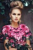 Belle fille dans la robe rose avec les cheveux bouclés sur un fond grunge Photographie stock