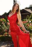 Belle fille dans la robe rouge élégante et la couronne luxueuse Photographie stock