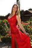 Belle fille dans la robe rouge élégante et la couronne luxueuse Photo stock